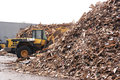Woodchip biomass heap shovel accumulate a pile of woodchips for use as a solid fuel Stock Image