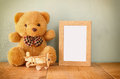 Wooden airplane toy and teddy bear over wood table next to blank photo frame. retro filtered image. ready to place photography Royalty Free Stock Photo