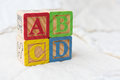 Wooden Alphabet Blocks on Quilt Spelling ABCD Stacked on Angle Royalty Free Stock Photo