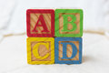 Wooden Alphabet Blocks on Quilt Spelling ABCD Stacked Royalty Free Stock Photo