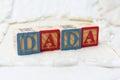 Wooden Alphabet Blocks on Quilt Spelling Dada Royalty Free Stock Photo
