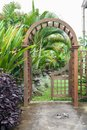 Wooden arbor with close on half gate in garden. Wooden arched entrance to the backyard. Royalty Free Stock Photo