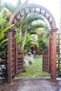 Wooden arbor with gate in garden. Wooden arched entrance to the backyard. Royalty Free Stock Photo