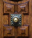 Wooden architectonic decoration this is a decorated part of a door with a golden doorknob Stock Photo