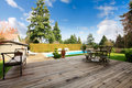 Wooden back poch overlooking swimming pool and trim wood porch with pation dining table set great view on Royalty Free Stock Image