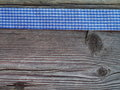 Wooden background with a checked ribbon blue Royalty Free Stock Image