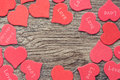 Wooden background of dark color with red hearts.