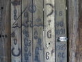 Wooden barn wall with branded signs gray planks of a former blacksmiths shop burned in letter figure combination marks and symbols Stock Photo