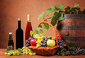 Wooden barrel with wine and fruits on the table Stock Photos