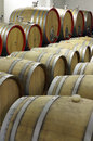 Wooden barrels for ageing maturing and storing of wine underground cellar close up with plastic corks industrial production Stock Images