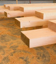 Wooden beams jointed ready for action and sawdust on floor Stock Photo