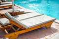 Wooden bed beside the pool beds are arranged behind s edge Royalty Free Stock Photos