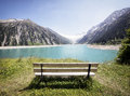 Wooden bench at a reservoir in austria Royalty Free Stock Photos