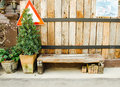 Wooden bench beside wood plank wall, Outdoor background. Royalty Free Stock Photo