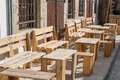 Wooden benches and tables outside on pavement Royalty Free Stock Photo