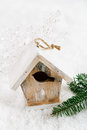 Wooden bird house christmas decoration on white snow background and snowflake Royalty Free Stock Photo