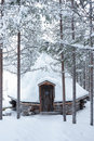 Wooden blockhouse with pyramid shape roof in winter in the white snow in the snowy forest of pine trees Royalty Free Stock Photo