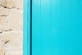 Wooden blue plank door texture near stone wall. Royalty Free Stock Photo