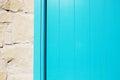 Wooden blue plank door texture near stone wall.