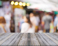 Wooden board empty table people shopping at market fair background. Royalty Free Stock Photo