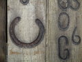 Wooden board with horseshoe branded a burned in and other signs in an old of a former blacksmiths shop Royalty Free Stock Photo