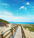Wooden boardwalk in capo testa on a clear day sardinia Royalty Free Stock Image