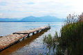 Wooden boardwalk at chiemsee lake bavaria shore with view to the alps Royalty Free Stock Photos