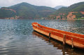 Wooden boat floating in lugu lake yunnan Stock Photos