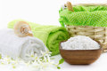Wooden bowl filled with bath salt and towels on the background Royalty Free Stock Photo