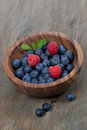 Wooden bowl with fresh blueberries and raspberries vertical close up Stock Photography