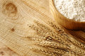 Wooden bowl full flour and wheat ears on background Royalty Free Stock Images