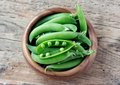 Wooden bowl full  of green peas pods. Top view. Royalty Free Stock Photo