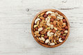 Wooden bowl with mixed nuts on white table from above. Healthy food and snack. Walnut, pistachios, almonds, hazelnuts and