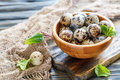 Wooden bowl with speckled quail eggs.