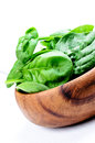 Wooden bowl of spinach on white table Stock Images