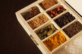 Wooden box full of spices closeup a with sections colorful focus is on turmeric dark background Royalty Free Stock Photography