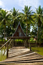 Wooden bridge across the water to the cottages have collapsed with coconut trees as a backdrop Stock Photo