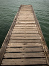 Wooden bridge from beach to the sea closeup old Royalty Free Stock Photo