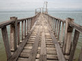 Wooden bridge from beach to the sea old Royalty Free Stock Photo
