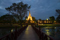 The wooden bridge conducting to ruins of the ancient Buddhist temple of Wat Sa Si in evening twilight. Sukhothai, Thailand Royalty Free Stock Photo
