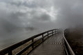 Wooden bridge engulfed in fog disappearing a thick Stock Photos