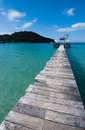 Wooden bridge from the island to the sea in moring Stock Photos