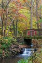 Wooden bridge over a creek with colorful fall foliage at Gibbs Gardens, Georgia.
