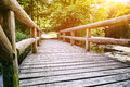 Wooden bridge over forest river at sunny day Stock Photography