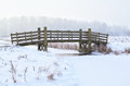 Wooden bridge over frozen river in winter Royalty Free Stock Images