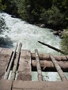 Wooden bridge over a mountain stream Royalty Free Stock Photo