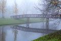 Wooden bridge over river in fog Stock Images