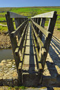 Wooden bridge over stream in countryside Royalty Free Stock Photos