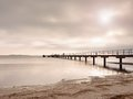 Wooden bridge at the sea at sunset.   Windless weather, peaceful silent day in bay. Royalty Free Stock Photo