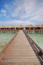Wooden bridge walkway leading to a row of overwater villa luxury with blue sky warm climate and clear water Stock Photography